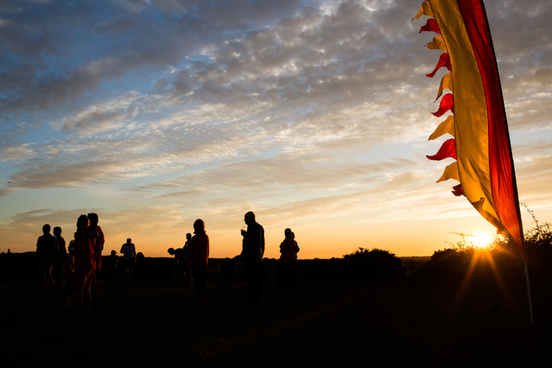 Silhouettes of people with festival flag and setting sun.