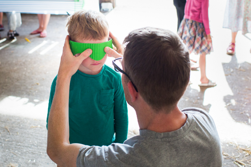 Man putting green mask over boy's eyes.