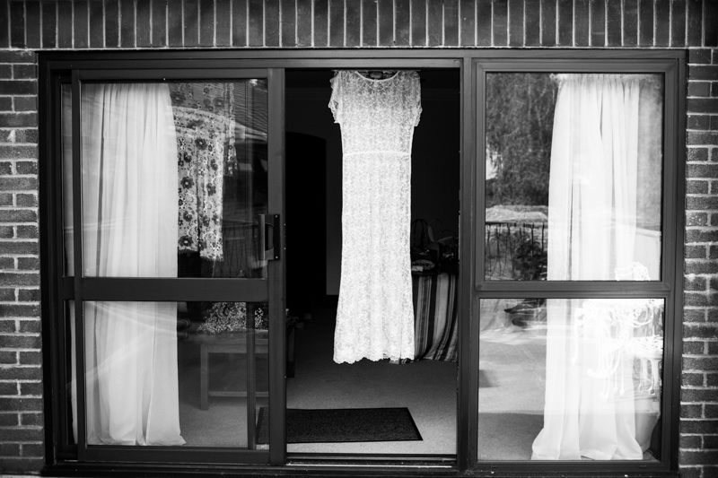 Wedding dress hanging in window.