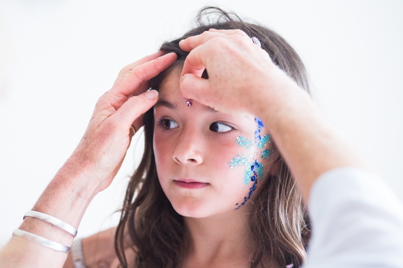 Girl having decorations put on her face.