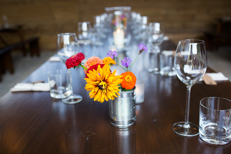 Colourful flowers on table in front of glasses.