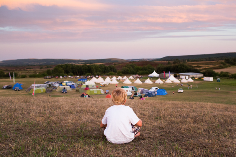 Boy with white shirt sitting on hill looking down on lots of tents.
