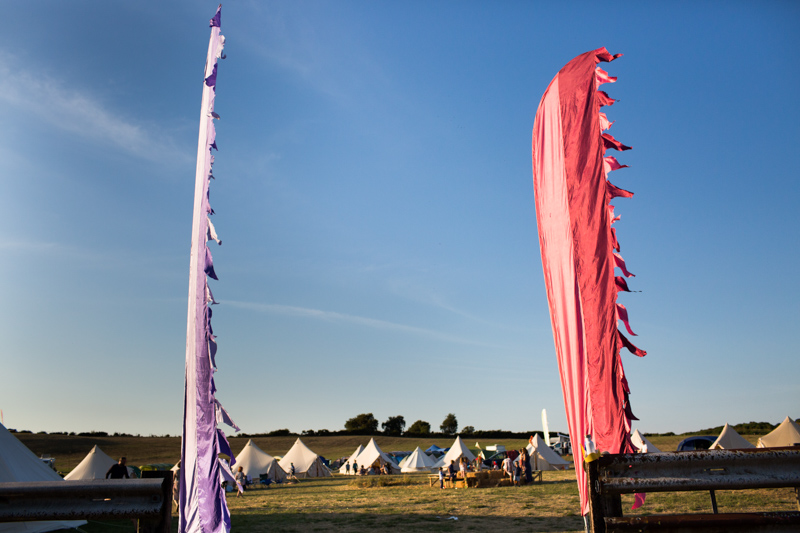 Two festival flags with tents in the background.