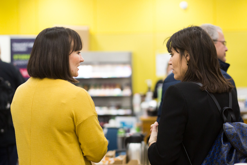 Two ladies talking in front of yellow wall.