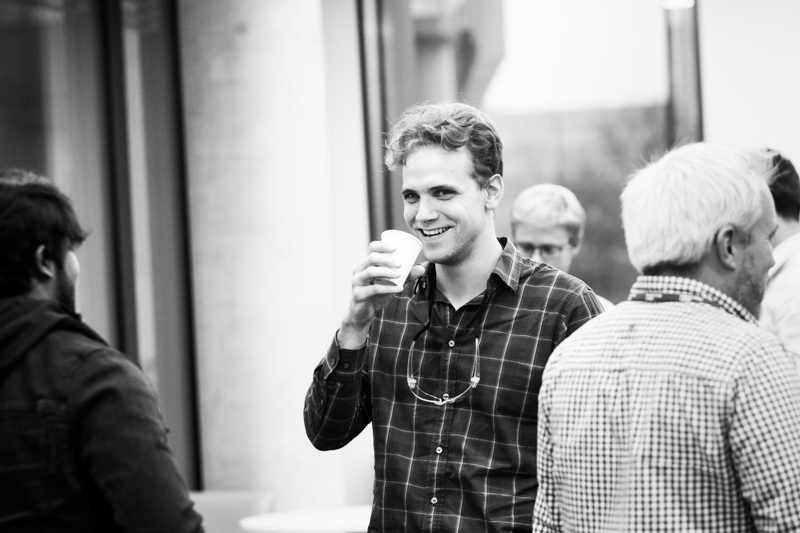 Man smiling and drinking a cup of tea.