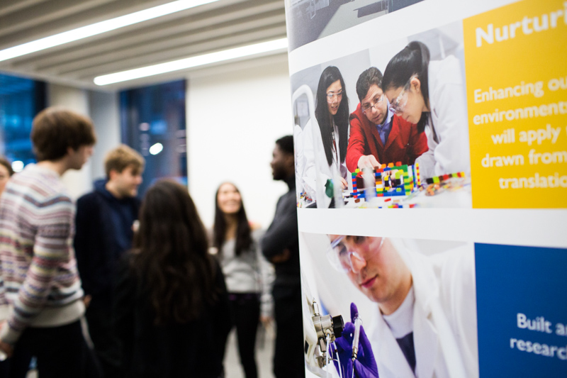 Scientists on poster with people in the background.