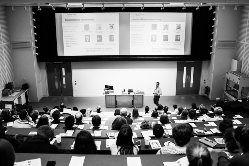 Man giving a speech in large lecture room.