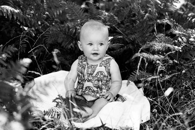 Little baby sitting amongst foliage on a white blanket.