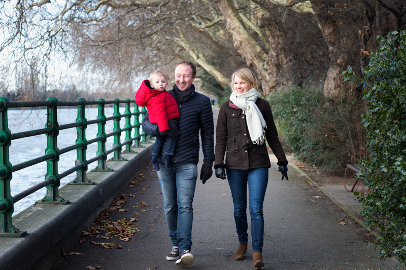 Mum, dad and baby in red jacket walking by the River Thames and green railings.