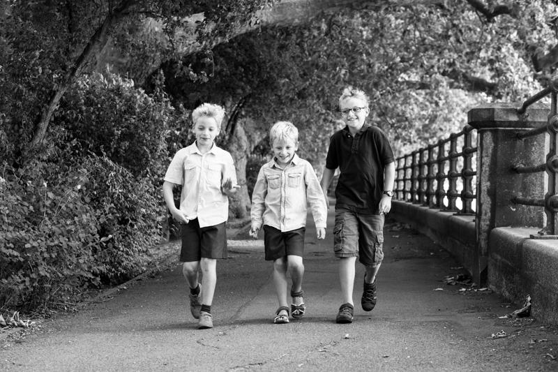 Three boys walking along next to railings and river.