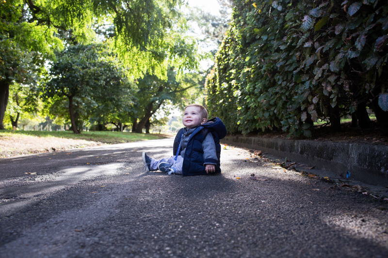 Little baby boy sitting on ground smiling with trees in background.