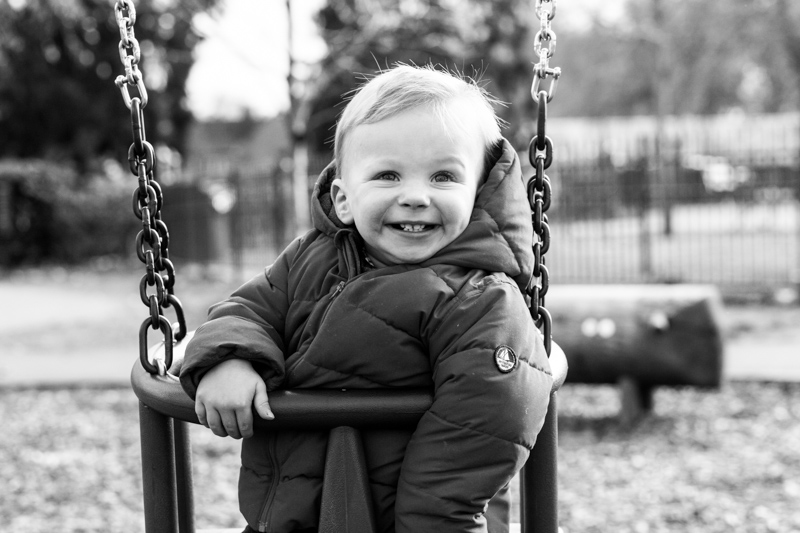 Very smiley baby boy sitting in a swing.