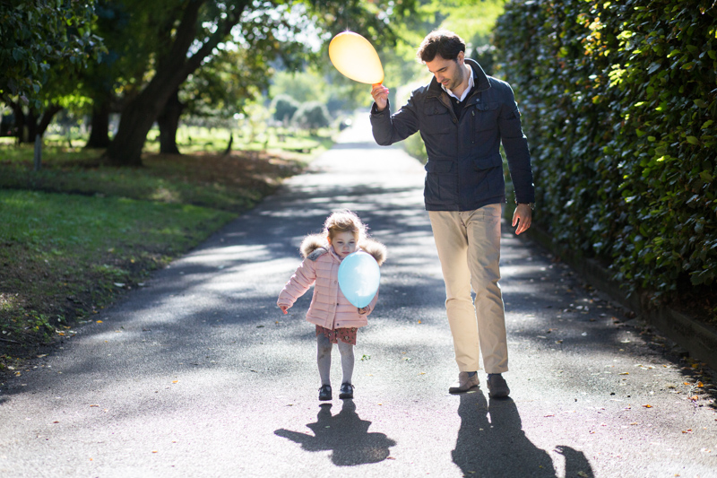 Dad and little daughter walking through the park holding balloons.
