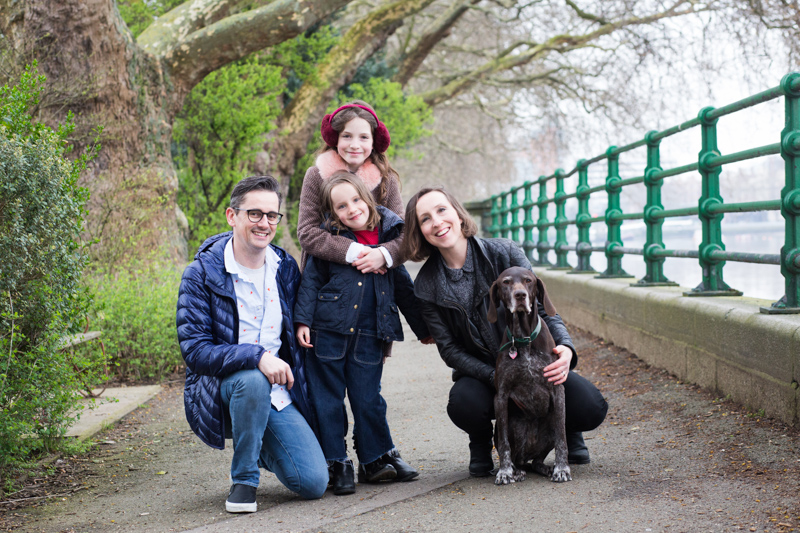 Mum, dad and two daughters and dog smiling next to green railings with trees behind them.