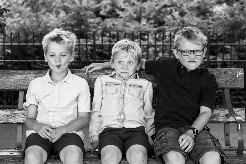 Three brothers pulling funny faces while they sit on a bench.