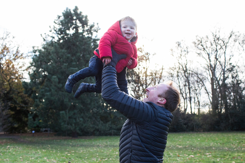 Man throwing his baby boy into the air in the park.