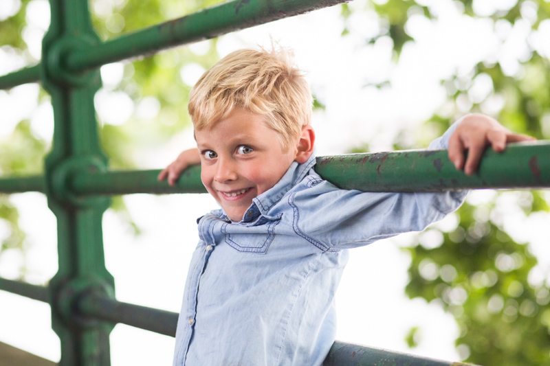 Boy smiling while holding onto green railing.