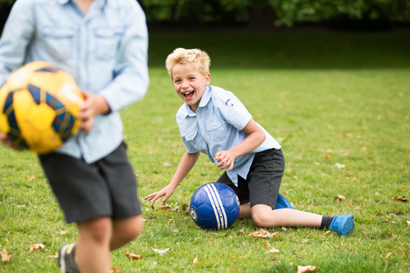 Laughing boy on the grass with a football.