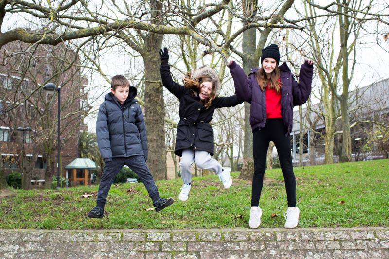 Three children jumping up in the air.