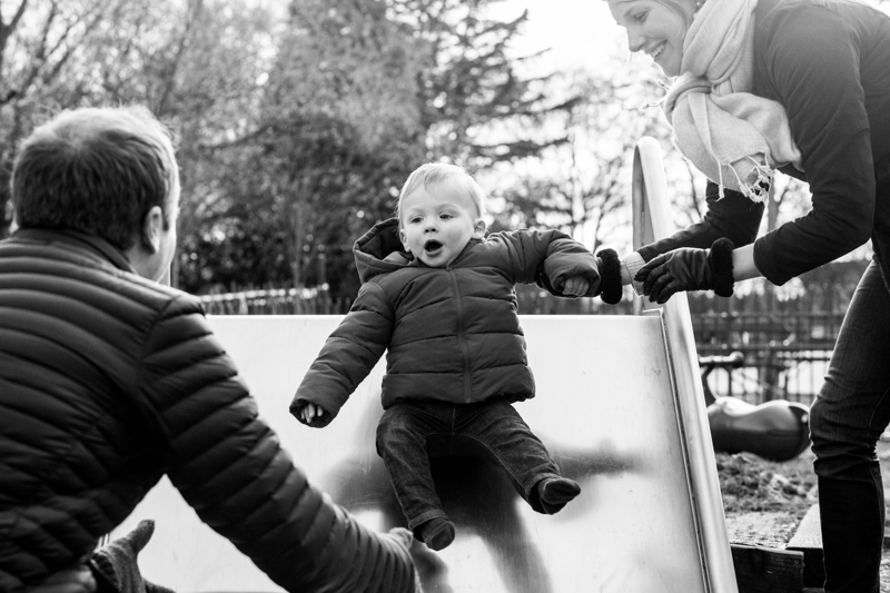 Baby going doing slide towards his mum and dad.