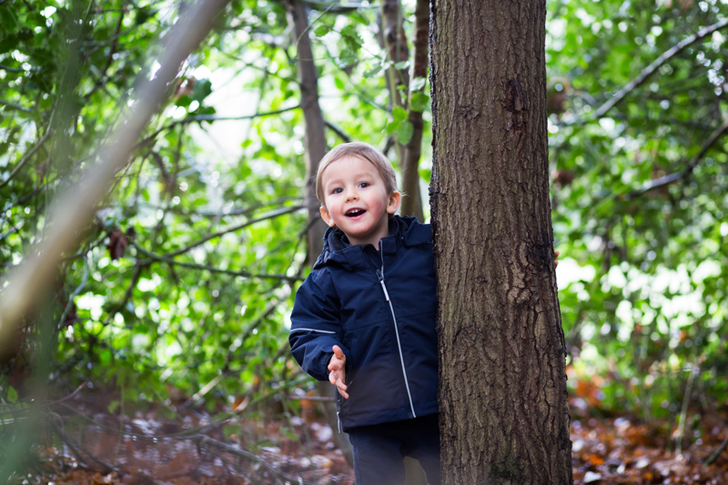 natural children's portrait of a little boy playing amongst the trees