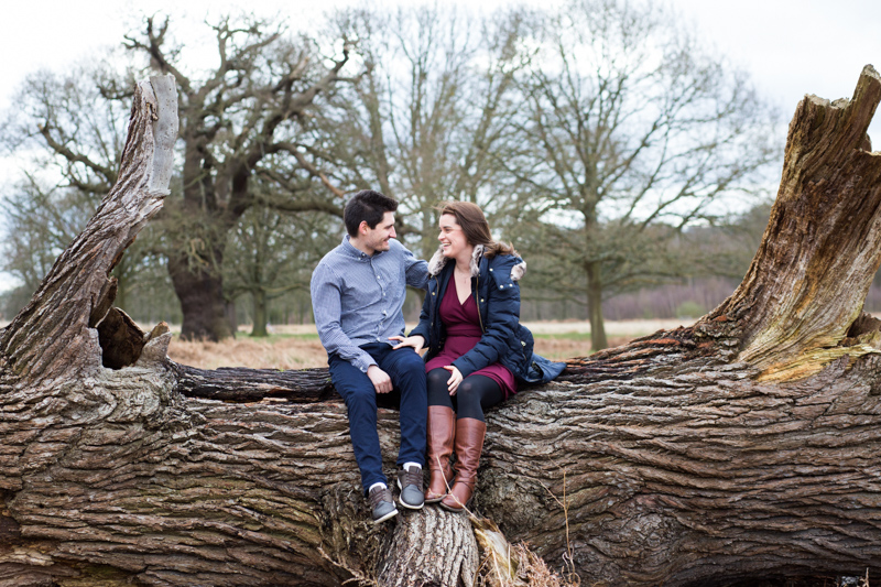 A man and lady sitting on a large fallen down tree trunk in the park