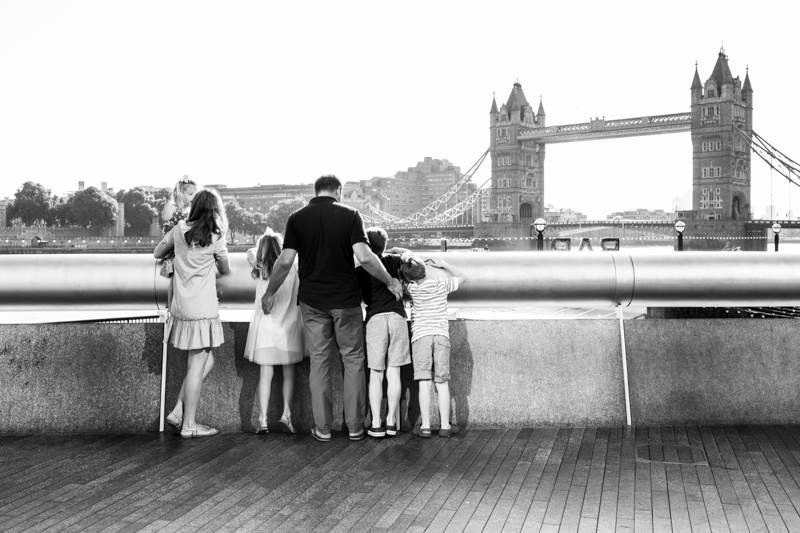 Family of five looking across the River Thames before Tower Bridge