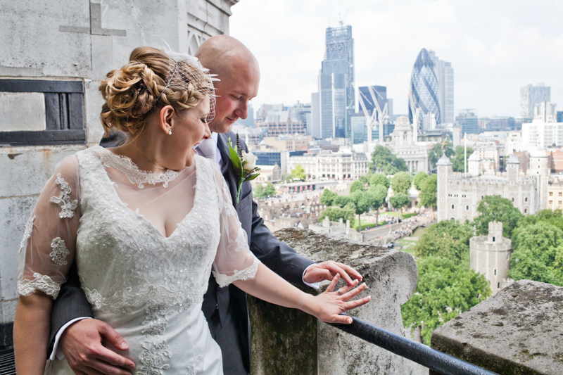 Bride and groom looking at her wedding ring with view of London behind them.