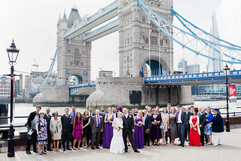 A big group wedding photo with Tower Bridge in the background.
