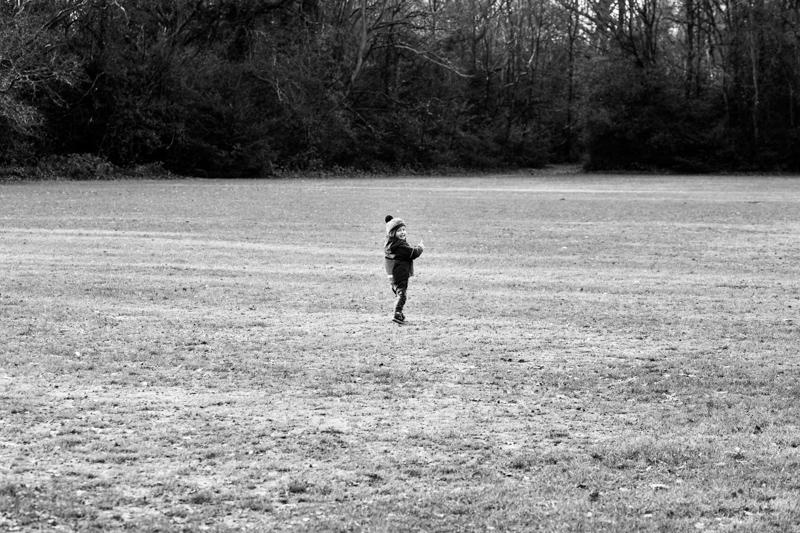 Little boy running across the grass.