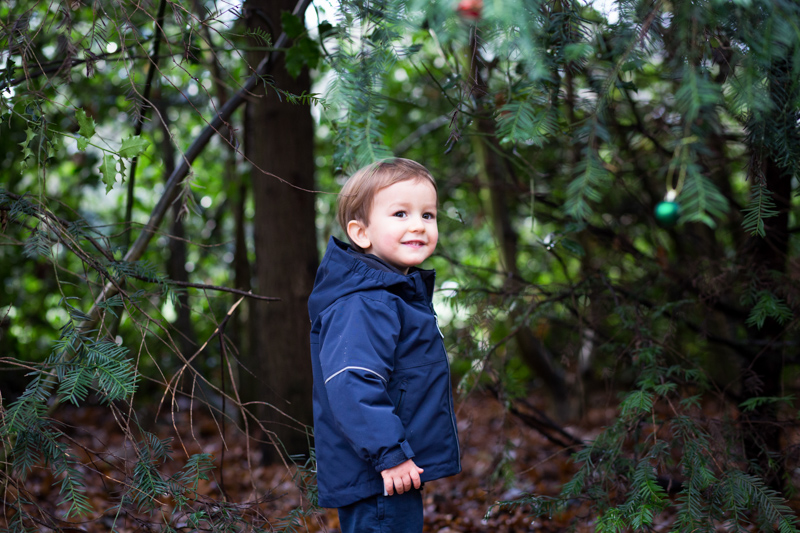 Little boy smiling amongst the trees.