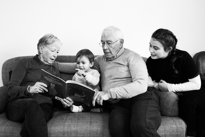 Grandparents reading a book with little boy and teenage girl.