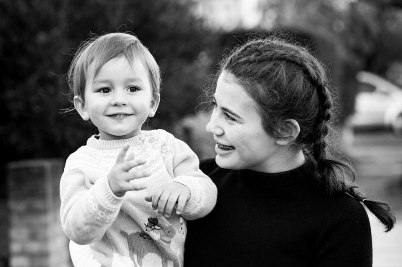 Teenage girl looking at little boy .