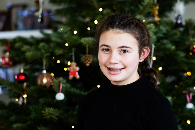 Portrait of a teenage girl in front of the Christmas tree.