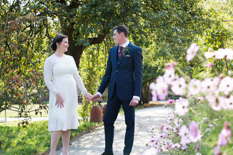A wedding couple holding hands and looking at each other amongst the trees and pink flowers.