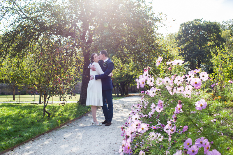 A groom kissing his new wife behind some pink flowers and in front of a tree.