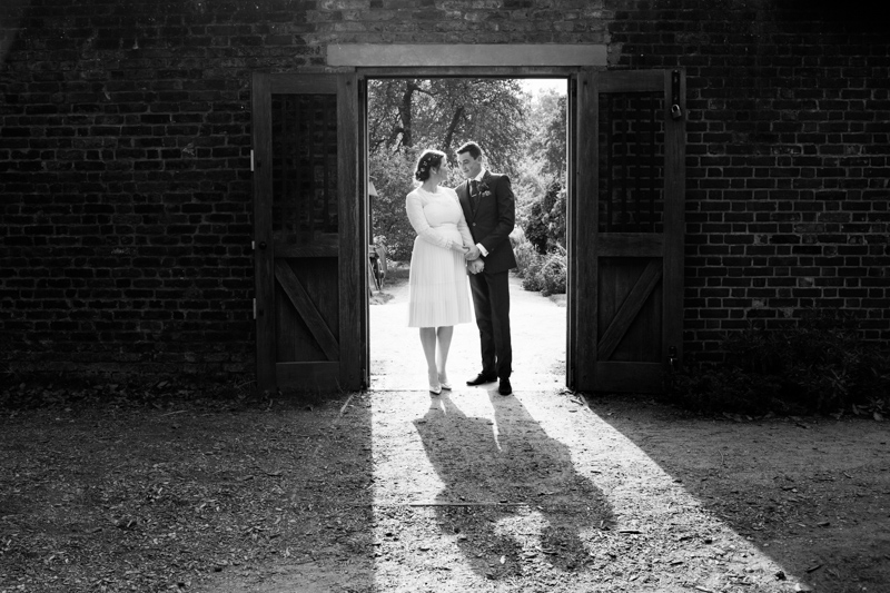 A wedding couple standing in the door way of a wall.