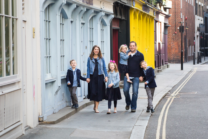 Mum, dad, two daughter and two sons walking hand in hand through a colourful street.