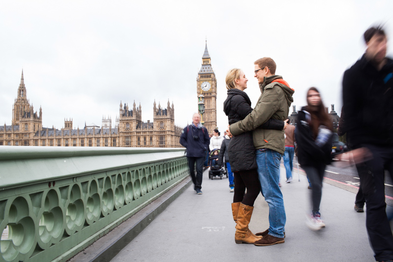 Couple standing on Westminster Bridge with the Houses of Parliament in the background.