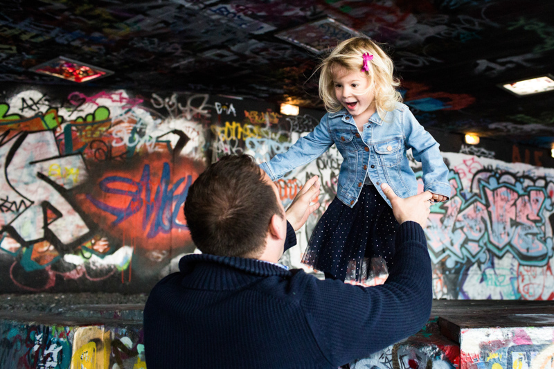 Girl about to jump into her Daddy's arms with graffiti in the background.