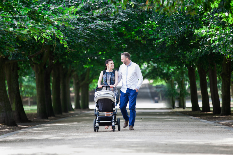 Man and lady pushing a pram through an avenue of trees.
