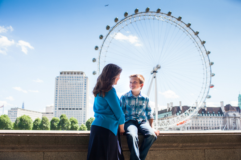 Mum and her son sitting on wall with the London Eye in the background.