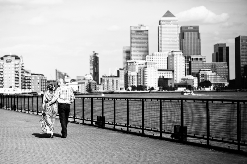 Man and lady walking by River Thames with Canary Wharf in the background.