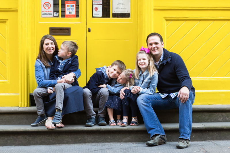 Family of six sitting on steps in front of a yellow shop.