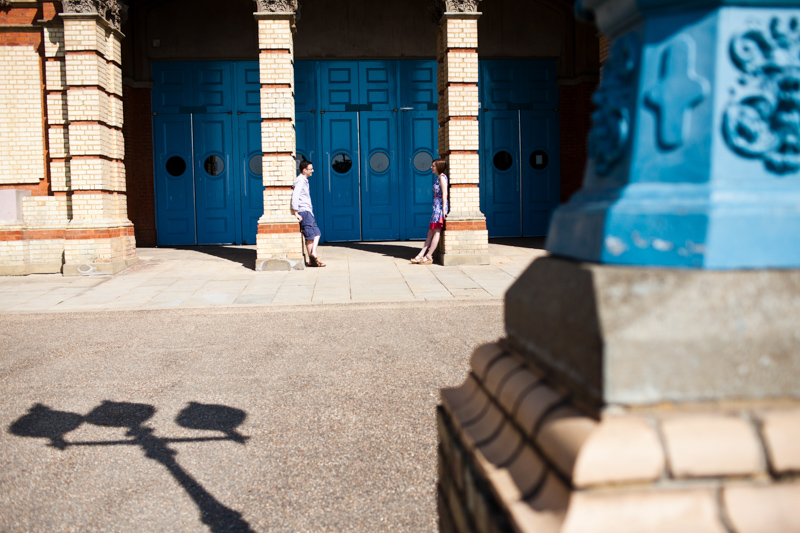 Couple looking at each other leaning on pillars in front of big blue doors.
