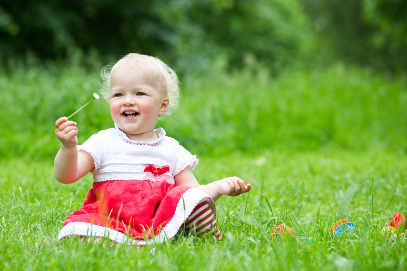 Little baby girl sitting on grass holding a daisy.