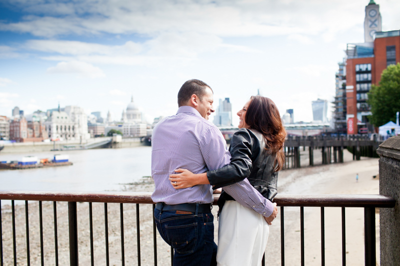 Couple looking at each other with the Oxo Tower and St Paul's Cathedral in the background.