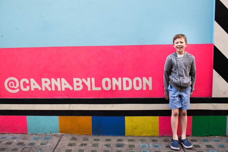 Laughing boy standing in front of Carnaby by London sign.