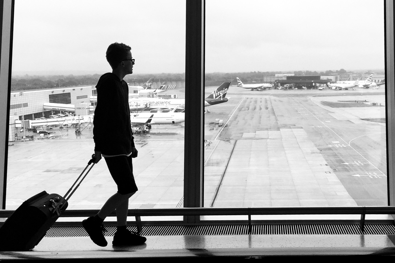 Silhouette of boy walking in airport with suitcase.