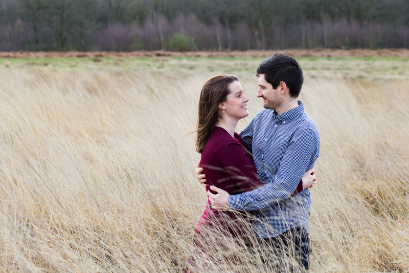 Couple looking at each other standing in very long grass.